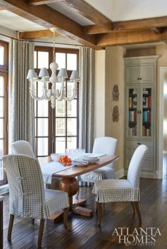 In the breakfast nook, French doors open onto a side courtyard. The dining table is custom through Nottingham Antiques, the chair fabric is Duralee and the chandelier is Currey & Company.