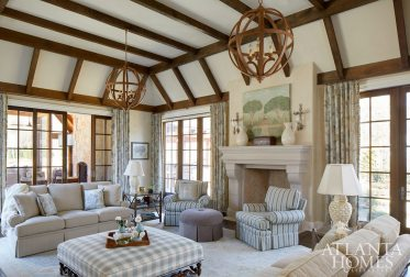 """Classic Charm In the living room of this Braselton, Georgia, residence, a lofty ceiling with rough-hewn beams creates a spacious feel, as do a wall of French doors that open onto a screened porch and outdoor kitchen area. Interior designer Gretchen Edwards outfitted the room with subtle pattern—as seen in the drapery, herringbone sofas and overscale-plaid coffee table. """"I love the combination of geometrics and different shades, but it's all really taken from the rug and drapery fabric,"""" the designer says."""