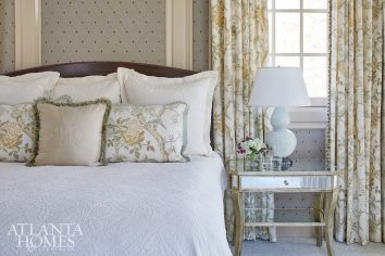 Fabric-paneled walls and wall-to-wall carpet from Underfoot Design create a softness and warmth in the master bedroom, despite the room's large proportions. The headboard is by Norman Hasty Carpentry, the drapery fabric is Thibaut and the bedside table is from Webb Marsteller. The chandelier is Visual Comfort through PDI, and the wall fabric is Duralee, upholstered by Bruce Wiley.