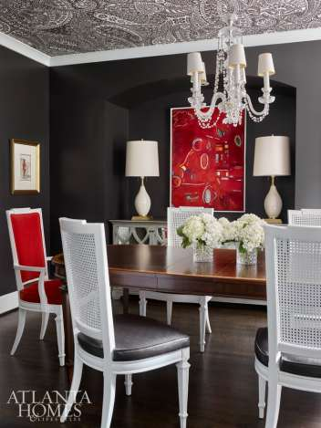 In the dining room, high-impact paisley wallpaper, deep gray walls and bold red flourishes make a statement.