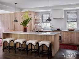 In their kitchen, the couple utilized surplus white oak (lime-washed by frequent collaborator and furniture craftsman Skylar Morgan) for custom cabinetry. Spindle-style stools from Bungalow Classic add a classic element to an island topped with the same local Cherokee marble that their firm, Square Feet Studio, used for countertops at West Egg Café and The General Muir.