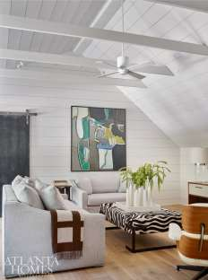 The recently renovated upper floor of the residence, which was formerly an unfinished attic space, now features a light-filled living area with a classic Eames lounger and a contemporary abstract gifted to the couple by Claudia Thompson, former owner of the shuttered Providence Antiques in Morningside.