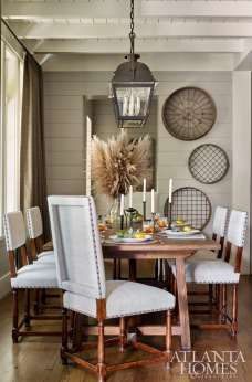 Open to the kitchen, the dining area features a double lantern light fixture by Paul Ferrante through Ainsworth-Noah. Grain sifters from Nicholson Gallery have been repurposed as artful accents. The chairs are from Jerry Pair and the table is custom.
