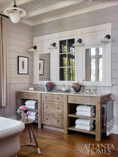 Function meets style in the master bath where Westbrook used trimwork to combine medicine cabinets and an interior window into one cohesive unit. The vanity is by Morgan Creek Cabinet Company. A soaking tub also adds a hint of luxury to laid-back lake life.