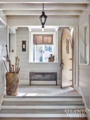 The foyer's footprint was kept small to create a cozy entrance. It gives guests a first glimpse of the nickel joint walls that run throughout the house for a clean, classic cottage aesthetic.