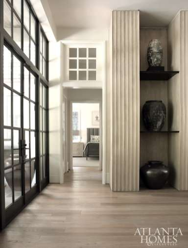 """The homeowners have long collected fine pottery, so the design team—led by interior designer Tish Mills Kirk and architectural designer Joel Kelly—delivered deceptively strong shelves for display. The white oak floors were a labor of love to reach the perfect finish. """"The color is awesome for hiding soil, as well as wear and tear from pets,"""" Mills Kirk says."""
