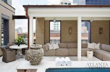 A rooftop deck featuring a pool, dining area and generous sectional sofa invites outdoor lounging.