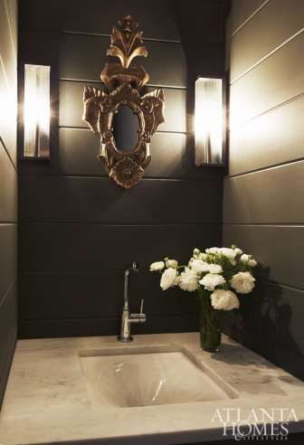 The powder bathroom is moody thanks to a dark, handsome hue and a French mirror.