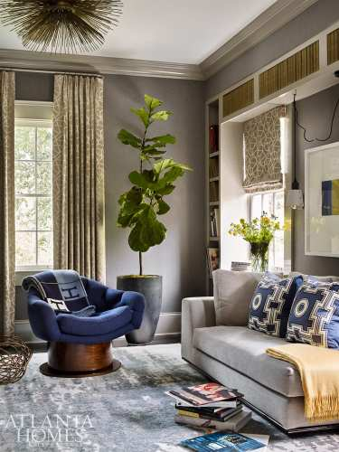 The husband's handsomely designed music room features custom built-ins and sumptuous seating. The throw is from R. Hughes.
