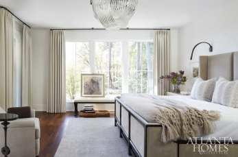 In the master bedroom, a crystal chandelier echoes the lines in the tailored wool draperies, which are a Holland & Sherry fabric.