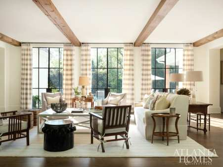 Paired with rustic ceiling beams, the drapery panels—rendered in Cowtan & Tout's Arno Stripe—help give this living room a sense of structure. Upholstery with soft curves, including Hickory Chair's Sutton sofa, has the opposite effect. Designer Jessica Bradley stain-treated their Mokum upholstery for daily wear-and-tear.