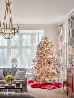 The homeowners, who have young children, carried the tradition of hand-flocking the tree into the next generation. The soft palette includes tufted sofas from Kravet in gray fabric from Thibaut, pillows from Acquisitions and draperies using Cowtan & Tout linen with embroidered medallions.