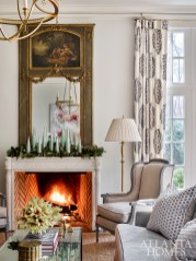 An antique trumeau mirror shares the space with Holland and Company wing chairs, Kravet sofas, a Visual Comfort chandelier and linen draperies in a Cowtan & Tout fabric