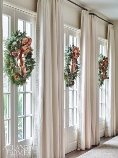 Wreaths adorned with sugared fruit decorate French doors that open to the lawn and pool.