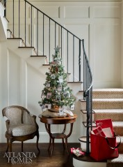 Rankin describes the interiors as timeless, livable and fresh. A small tree with sterling silver ornaments that are replicas of past family Christmas cards, serves as a point of reflection in the entry; the iron railing is by Calhoun Design & Metal Works.