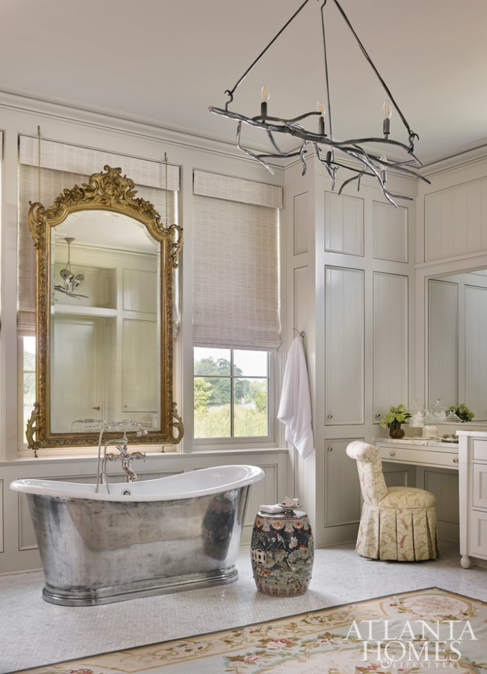 A suspending mirror is the master bath's focal point. Other winsome details include an antique garden stool and a custom light fixture by Jason Smith of Smithworks Iron & Design.