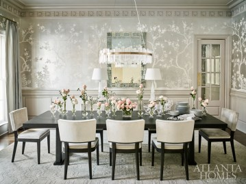 A traditional wall covering by Gracie Studio juxtaposes the modern table and chairs from Christian Liaigre in the formal dining room. The rock crystal chandelier is by Coup D'Etat from R Hughes.
