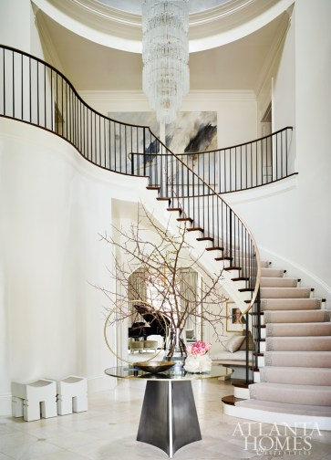A custom table complements the new custom stairway railing by Charles Calhoun of Calhoun Design & Metalworks in the front entry. The parchment-covered stools are from Kasler's Hickory Chair collection.
