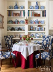 The blue-and-white chairs with a needlepointlike tapestry from Brunschwig & Fils surround the table year-round. Folk art figurines inspired by childlike toys (created by Debbee Thibault and through Erika Reade Ltd.) update the bookshelves for the season. Tulips and holly berries combine in the floral centerpiece by Susan Massar of The Flower Lady, which Bentley placed in a silver Gorham wine cooler, circa 1885, from Beverly Bremer Silver Shop.