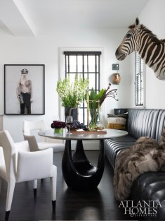 A dining table by Jiun Ho pulls double-duty as full-scale sculpture in Hughes' dining area. A pair of modern chairs by Natasha Baradaran are covered in a Holland & Sherry linen. (The fur throw and mounted zebra are both faux.)