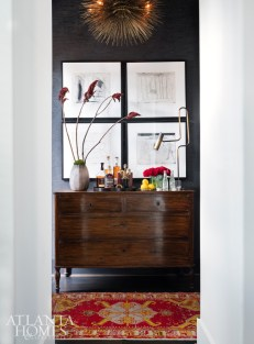 Jean de Merry's modern classic Lumiere chandelier shines over an antique chest Hughes has repurposed as a bar, along with an antique Oushak rug from Moattar. The quartet of works on paper is from Townhouse by Robert Brown.
