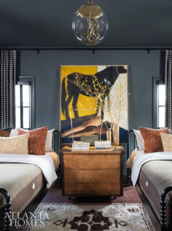 To provide his guests the ultimate in comfort, Hughes combined two small bedrooms to make a single, immense one. An antique pine trunk is tucked between the two Jenny Lind beds from Crate & Barrel. The reproduction wool military blankets are BoBo Intriguing Objects.