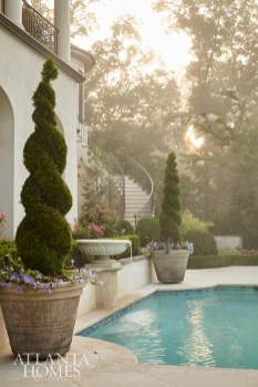 Early morning mist envelopes the outdoor living area, which includes a quatrefoil-shaped pool and boxwood hedges separating the pool from the surrounding gardens.