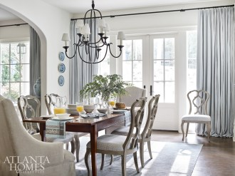 The breakfast room is softened with sinuous chairs with a check fabric from Romo, a pair of upholstered armchairs and an antique table. An iron chandelier keeps the space from feeling too formal.