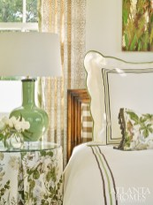"The palette throughout the house draws from the lakeside setting and rich foliage. ""I'm drawn to soothing colors—nothing too bold,"" says Elizabeth. In a guest bedroom, a cheerful floral print from Lee Jofa appears in a skirted table and bed pillow. The windows in that same fabric are edged in a Scalamandré trim in a color that plays off the bedside lamps by Joseph Konrad."