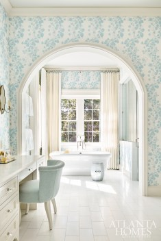 A beautiful arched opening frames the entrance to the bath and shower space. Classic wallpaper from Waterhouse Wallhangings adds a little liveliness while keeping the spa-like look. The vanity chair is by Hickory Chair covered in a Donghia fabric.