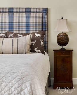 below One of the son's bedrooms makes a statement with Ralph Lauren plaid shams, bedding in taupe hues from Traditions Linens and a custom upholstered headboard with nailhead detailing.