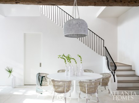 To create a place of refuge for her busy client, interior designer Melanie Turner outfitted this Alys Beach abode with elements of California cool. In the dining alcove, a basket-style light fixture holds court above a dining table from Design Within Reach.