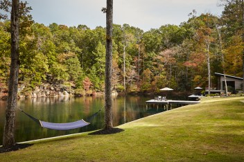 "The property offers complete privacy for its owners and guests. Overlooking the lake, with the sound of the waterfall just beyond, Quinn's tub for MTI Baths takes ""forest bathing"" to the next level, he says. Landscaping by Matt Fulton of Willow Oaks Landscapes."