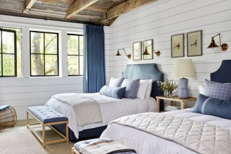 The boys' bedroom features custom upholstered beds in a Schumacher fabric. Just above hangs a framed set of fly-fishing lure prints in a nod to one of the family's favorite pastimes. The benches are from Bungalow Classic and feature a Holland & Sherry plaid upholstery.