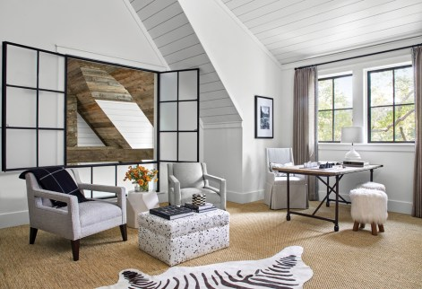 Accessible through the master suite, the loft was designed as a personal and private space for the husband to catch up on work. The black- and-white photography was taken by the wife, and the sisal carpeting, found throughout most of the home, is by Stark.