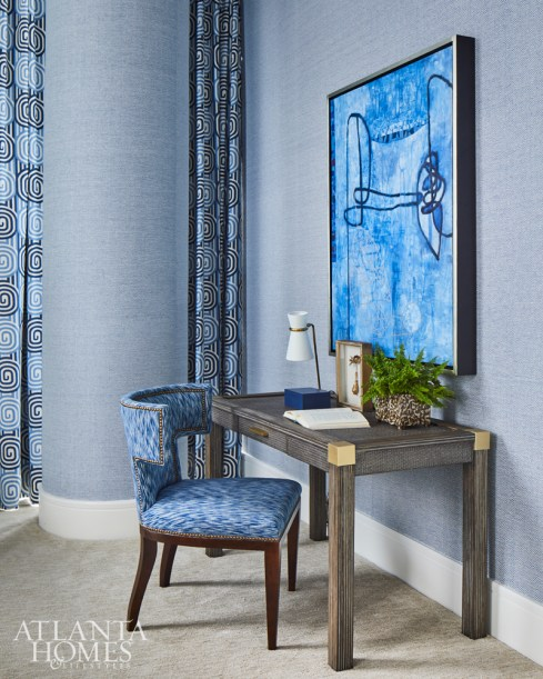 To make this bedroom's structural column less conspicuous, Howard wrapped it in a Phillip Jeffries wallcovering. A desk by Palecek and chair by Mr. and Mrs. Howard for Sherrill Furniture offers the homeowner a quiet spot to work.