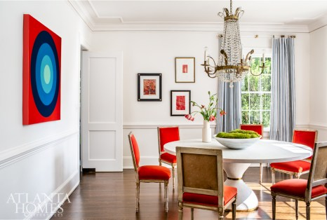 Interior designer Lee Kleinhelter incorporated pops of red-orange into the dining room of this circa-1935 home through velvet-upholstered chairs (sourced from Parc Monceau and re-covered in a Knoll velvet) and Stephanie Henderson's Target painting. Overhead, an antique chandelier adds a classic touch. The drapery is Miles Redd for Schumacher in Capri.