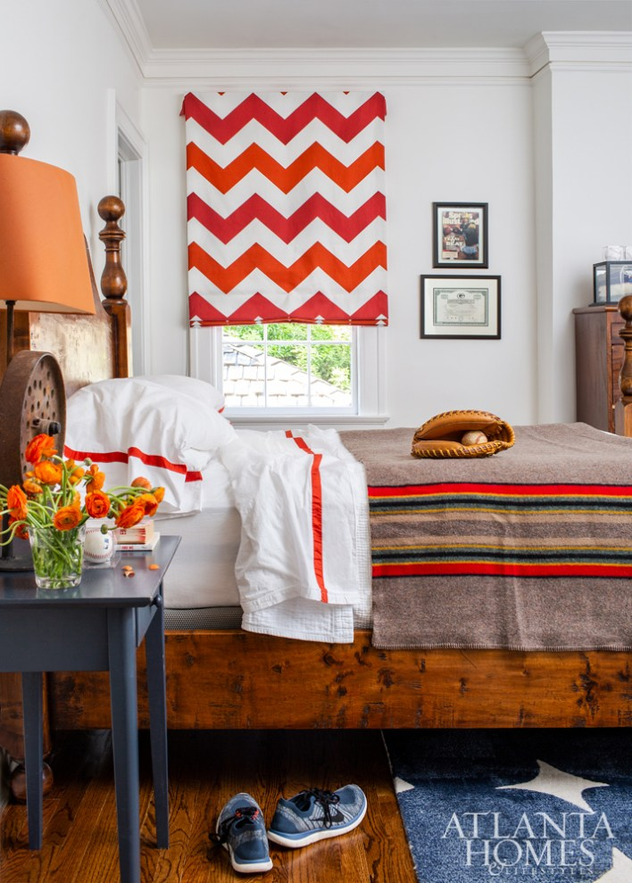 This teen bedroom nods to the family's love of sports, featuring signed memorabilia and a playful red-and-blue palette. The drapery fabric is Schumacher and the bedding is Peacock Alley.