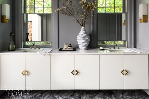 Painted Benjamin Moore's Whale Gray, the master bathroom features a custom herringbone-cut marble and spacious floating vanity. Adjustable custom mirrors were placed within the existing windows to provide privacy without blocking natural light.