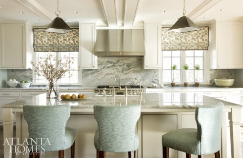 In the kitchen, quartzite backsplash and countertops take center stage, acting like abstract art for the space. Pendant lights from The Urban Electric Co. lend an elegant feel while the Galbraith & Paul Roman shade fabric sets a lively tone.