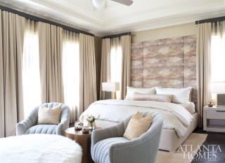 In the master bedroom, a wallcovering by Phillip Jeffries, draperies by Pindler and sheers by JF Fabrics create an enveloping retreat. The plush swivel chairs are from Arteriors.