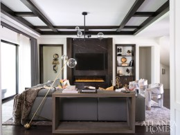 A chandelier from RH illuminates the cozy great room, where a sectional sofa from Natuzzi and club chairs by Moss Studio covered in fabric by Lee Jofa create a comfortable conversation area in front of the newly redesigned fireplace.