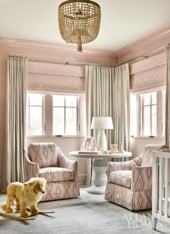 A nursery is surrounded by soft shades of pink, including a pair of swivel rockers from Gabby covered in an embroidered linen by Jane Churchill, and walls painted Benjamin Moore's Sonoma Clay.