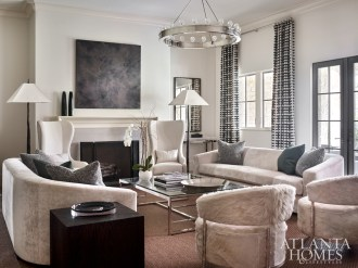 In one of the home's generous living spaces, pictured and opposite, a made-for-conversation seating arrangement includes Holly Hunt sofas, a pair of hide-covered chairs from Bradley and wing chairs by Ironies, which flank the fireplace. All of the art hanging is from Townhouse by Robert Brown.