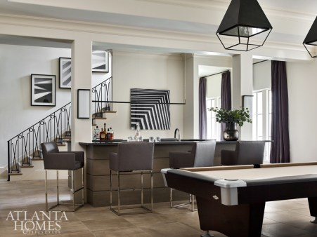 The redesigned terrace level features both open areas for entertaining and more intimate spaces, including a downstairs living room, pool table, wine cellar, bar and golf simulator. The art is from Townhouse by Robert Brown. The bar and wine cellar cabinetry was designed by Cardea Home.