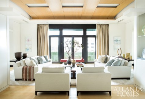 Suzanne Kasler Interiors fostered a sense of serenity in the elegant formal living room with plush, clean-lined Christian Liaigre furnishings accented by a red leather bench and white millwork.