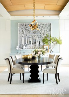A bespoke brass chandelier from Hudson Furniture makes a statement in the dining room, which is furnished with a dark wooden table and velvet-covered chairs. The custom wool rug is from Mansour.