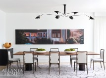The custom dining table by Skylar Morgan Furniture can be reconfigured into three small tables or remain one large banquet table to accommodate a crowd. A hyperrealist painting by Damian Loeb is a conversation starter.