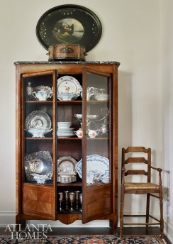 Treasures fill an antique vitrine in a corner of the dining room; it is topped with a papier-mâché tray from Scott Antique Markets.