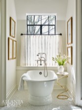 The soaking tub area is adorned with drawings of antique furniture and a side table sourced from Grizzell & Mann.